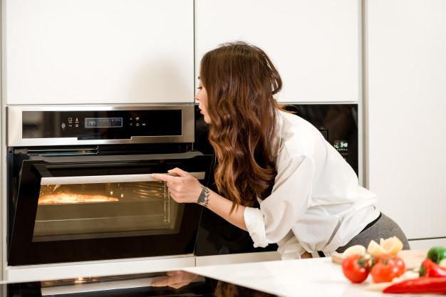 mulher cozinhando forno cozinha sp